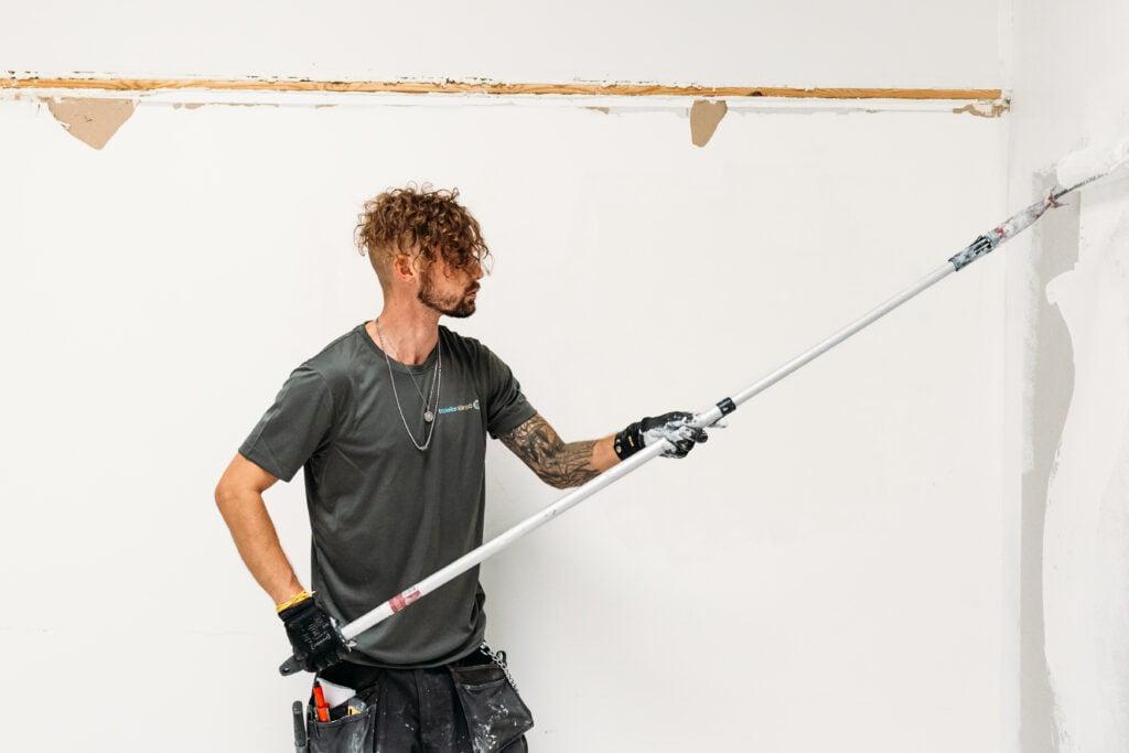 Tapiolan Lämmön työntekijä maalaamassa.