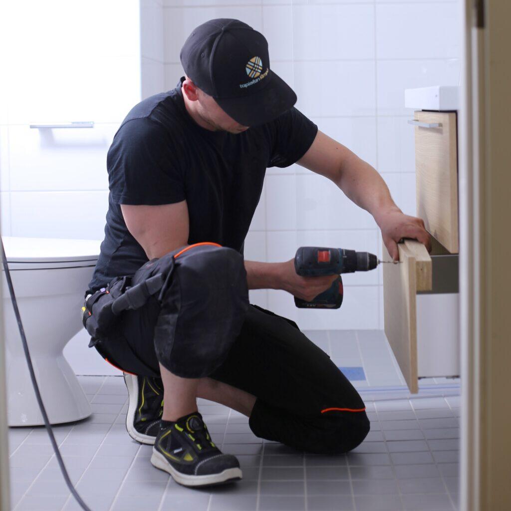 Remonttityöntekijä poraamassa kylpyhuoneen hyllyä